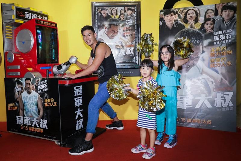 亮哲(左)與腕力機PK 女兒應援團小菩(右)小緹(中)拿彩球賣力為爸爸加油打氣